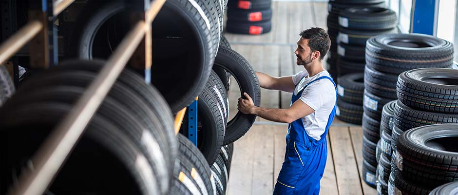 mechanic selecting tyre from warehouse shelf